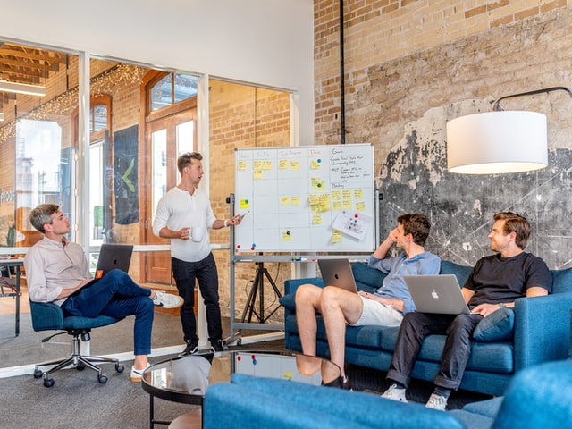 A group of business staff in casual dress attend a meeting and put ideas on a whiteboard. Keyword research is an ongoing process whose best practices are continually evolving.
